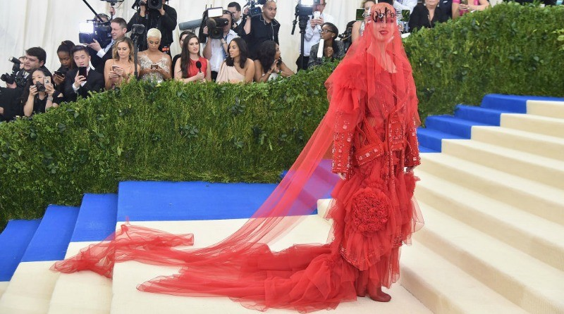 Katy Perry is covered head to toe in red standing on steps in front of the paparazzi.
