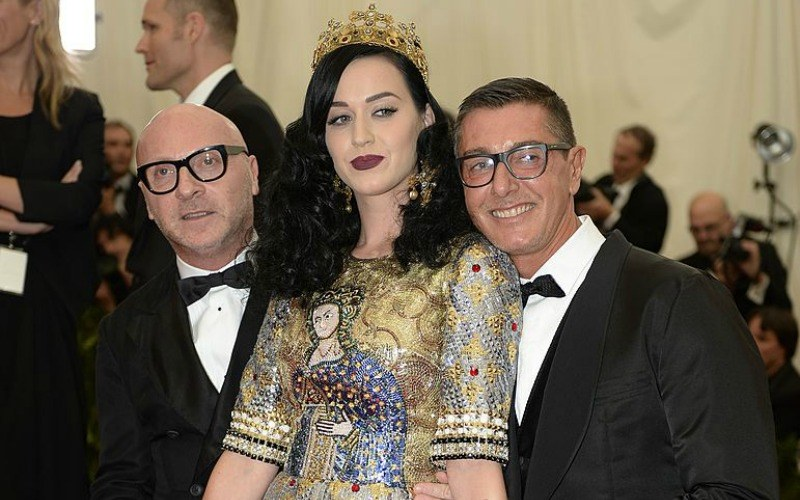 Katy Perry is in a gold dress and is wearing a crown with two men in tuxedos beside her.