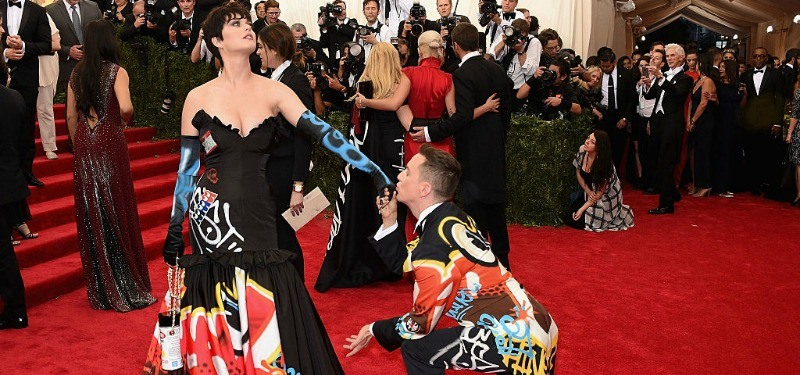 Katy Perry and Jeremy Scott are in matching dress and suit jacket as he is one bended knee kissing her gloved hand.
