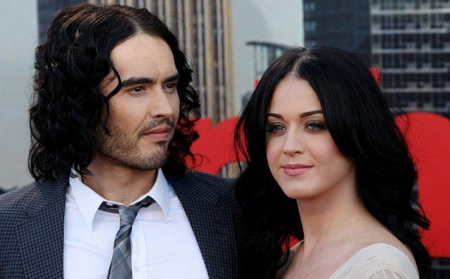Russel Brand and Katy Perry are posing next to each other on the red carpet.