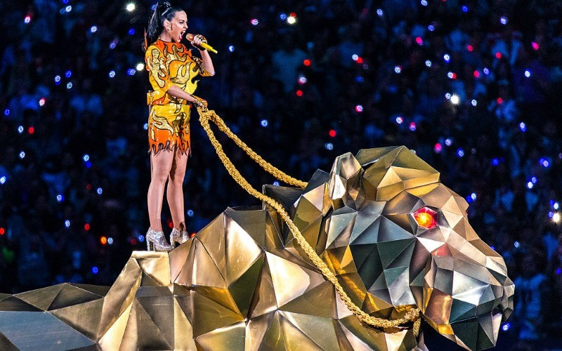Katy Perry is in a shirt and shorts that are made to look like fire while holding the reigns to a metallic animal.