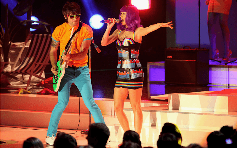 Katy Perry is singing in a purple wig and a rainbow dress.