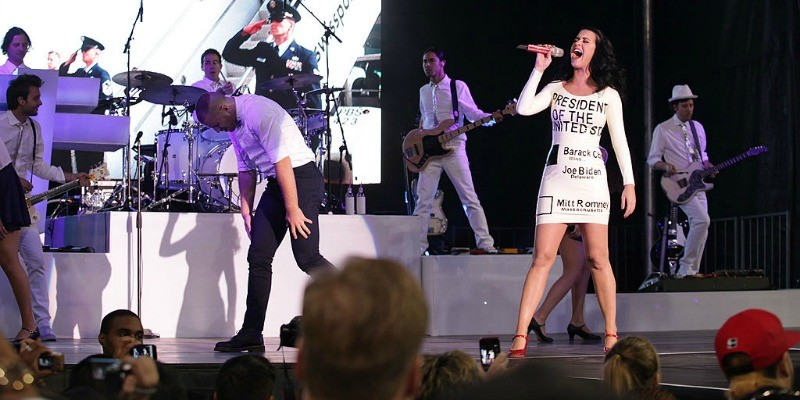 Katy Perry is singing on stage in a dress that looks like a voting ballot with President Obama filled out.