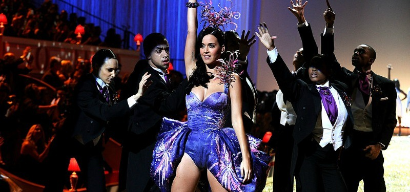 Katy Perry is in a purple dress with a fireworks hat.