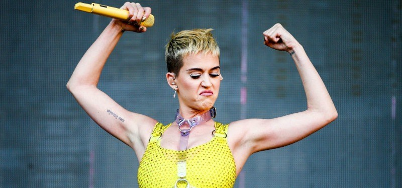 Katy Perry flexing her muscles in a yellow top holding a yellow microphone