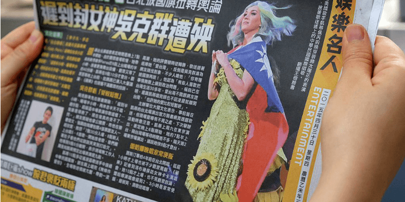 A hand holding a Chinese newspaper which shows Katy Perry wearing a sunflower dress and using a flag as a cape.