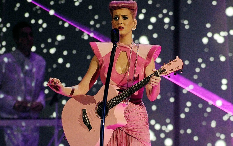 Katy Perry has pink hair and is an all pink outfit on stage as she holds a pink guitar.