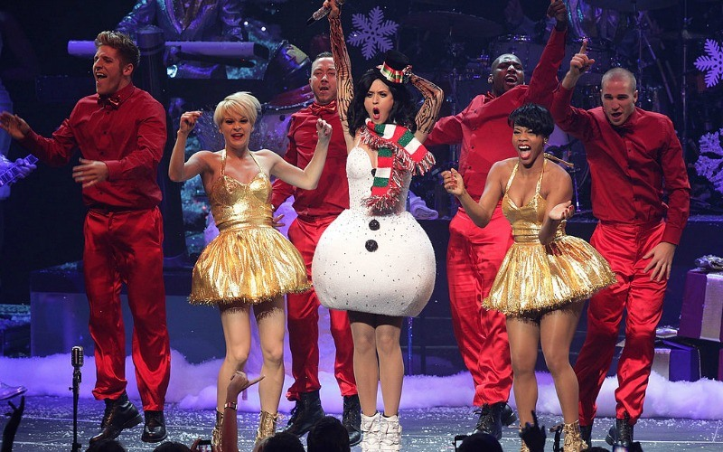 Katy Perry is dressed as a snowman and has one hand up in the air on stage.