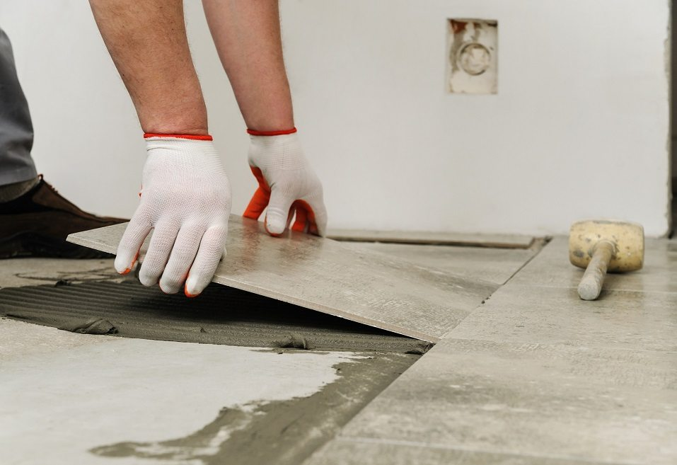 Worker placing ceramic floor tile