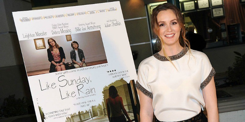 Leighton Meester is smiling next to a movie poster.