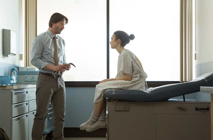 Lilly Collins sits on a doctor bed and talks to Keanu Reeves in To the Bone