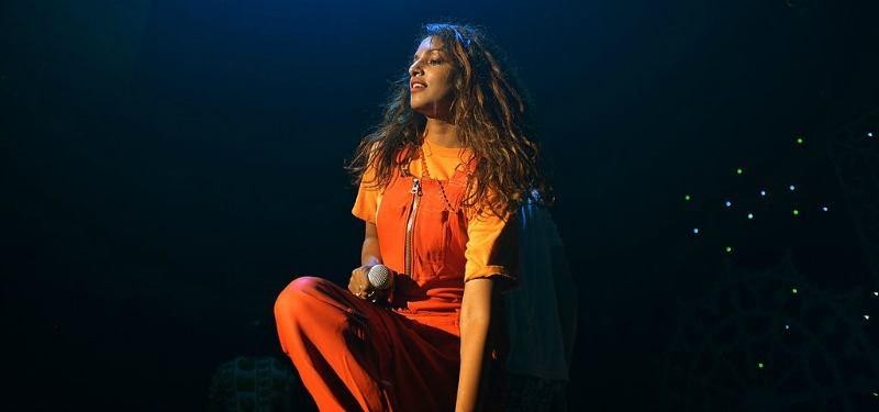 M.I.A. is in orange overalls and is holding a microphone on stage.