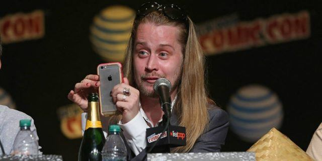 Macaulay Culkin is sitting on a panel and is taking a picture with his phone.