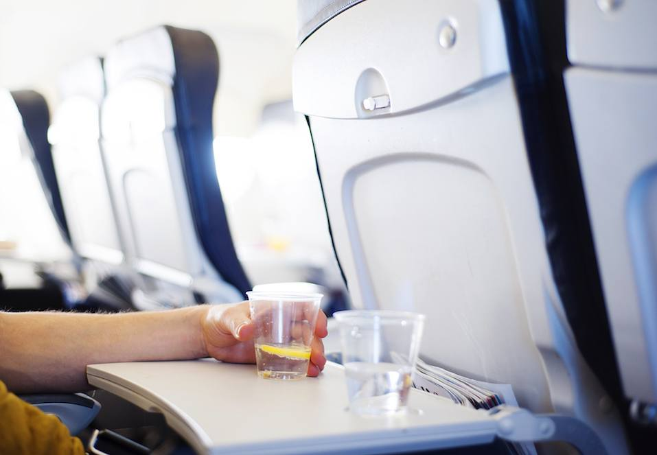 Happy man seating in the aircraft and drinking a beverage
