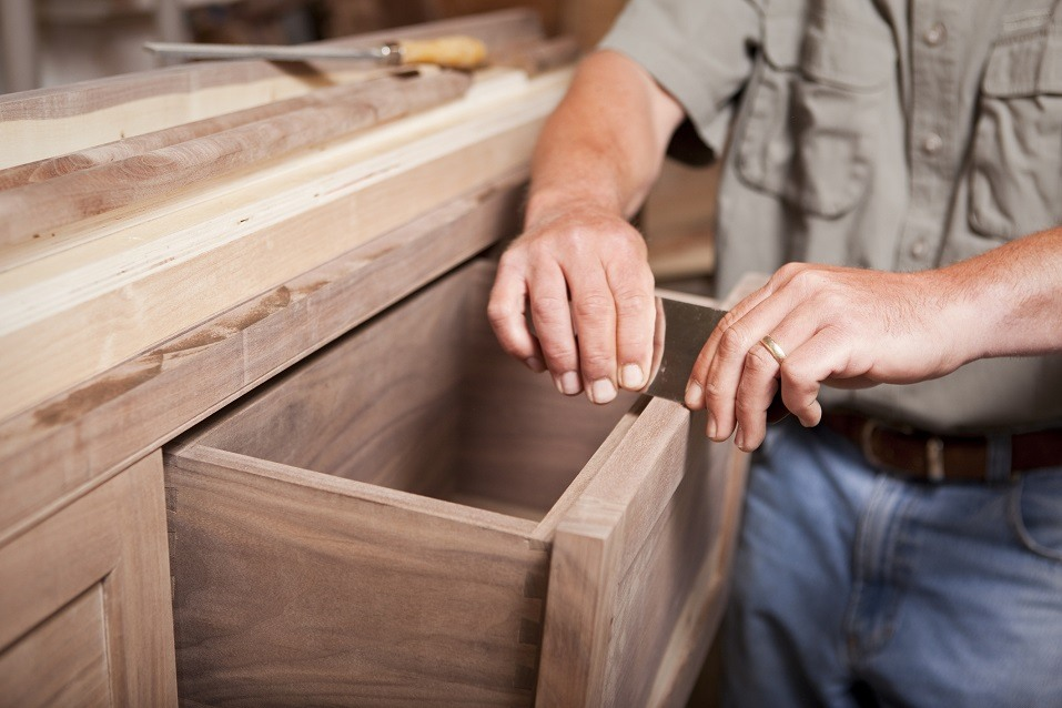 cabinet maker smoothing out a drawer for a kitchen remodel
