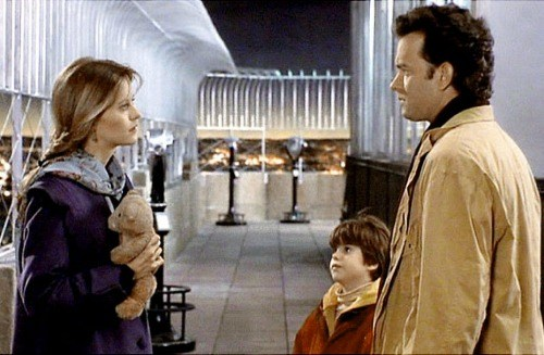 Tom Hanks stands next to a young child while talking to Meg Ryan in Sleepless in Seattle