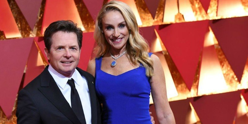 Michael J. Fox is in a black suit and Tracy Pollan is in a blue dress on the red carpet.