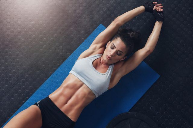 Muscular woman doing stretching workout on exercise mat.