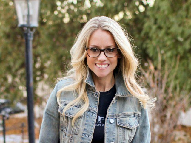 Nicole Curtis stands outside and smiles in a denim jacket.