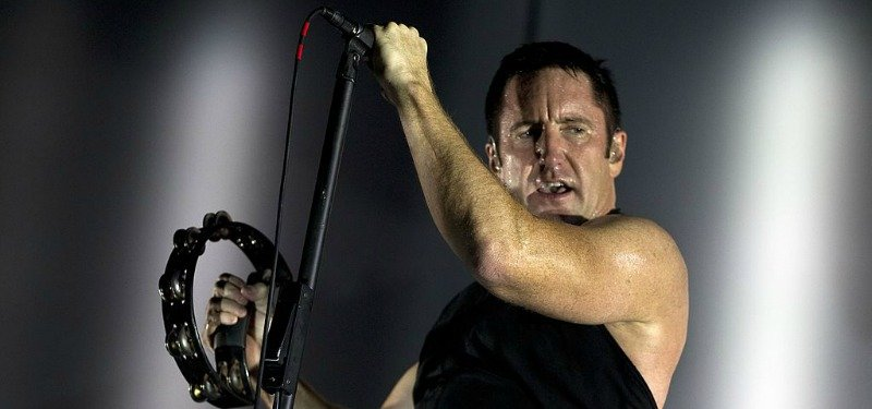 Trent Reznor is holding a microphone in one hand and shaking a tambourine with the other on stage.