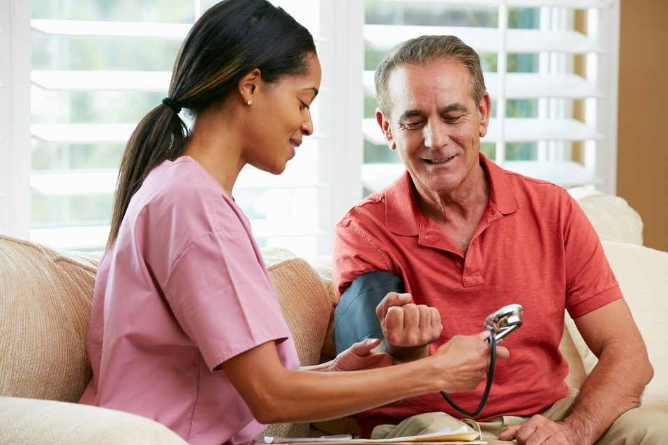 Nurse Visiting Senior Male Patient and checking blood pressure