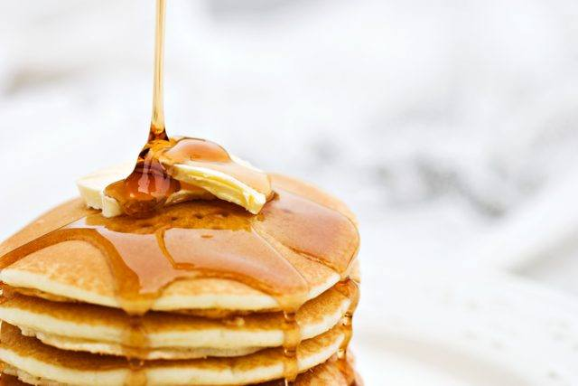 Pancakes with focus on syrup and butter.