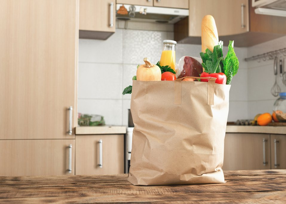 Paper bag full of food on a wooden table