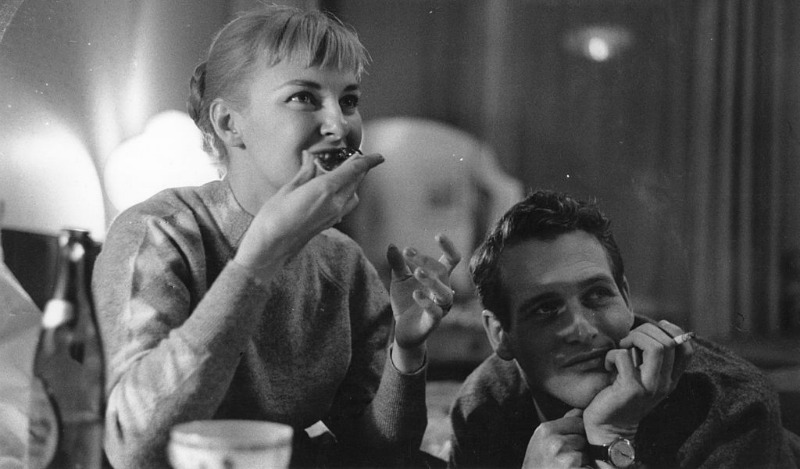 Joanne Woodward is eating while Paul Newman is next to her.