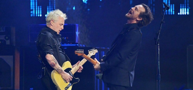 Mike McCready (L) and Eddie Vedder are playing guitar and bass facing each other on stage.