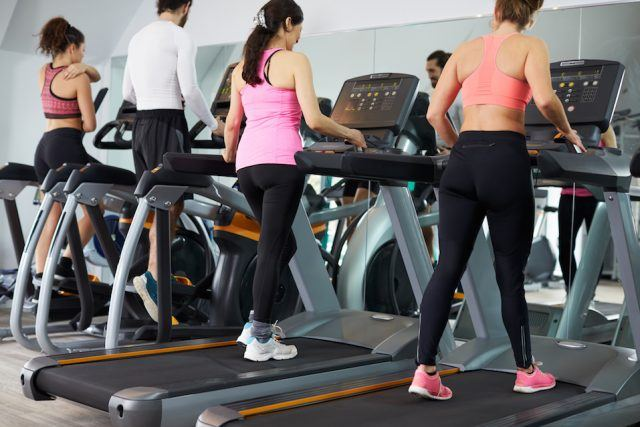 A group of people do cardio on equipment at a gym.