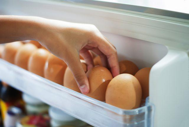 A person picks up eggs from a container.