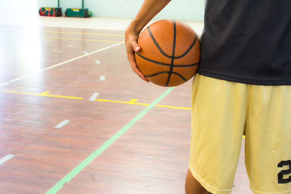 Playeer with basketball ball in gym