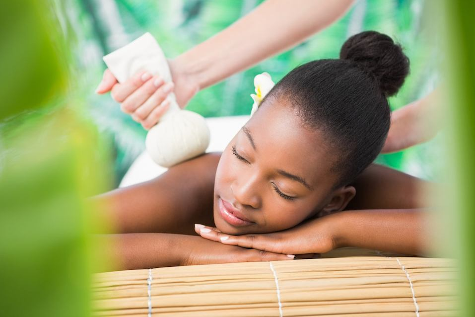 woman enjoying a herbal compress massage