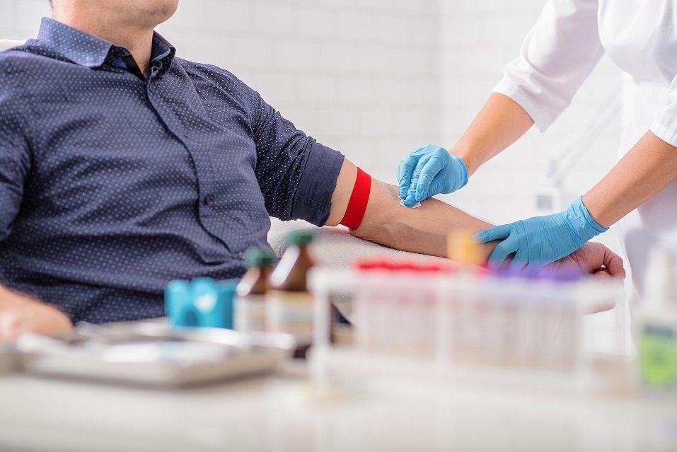 nurse disinfecting male arm
