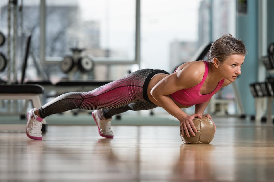 female athlete performing push-ups on a medicine ball