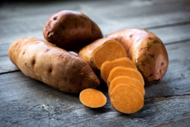 Raw sweet potatoes on a wooden table.