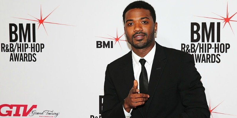 Ray J is posing in a suit and pointing on the red carpet.