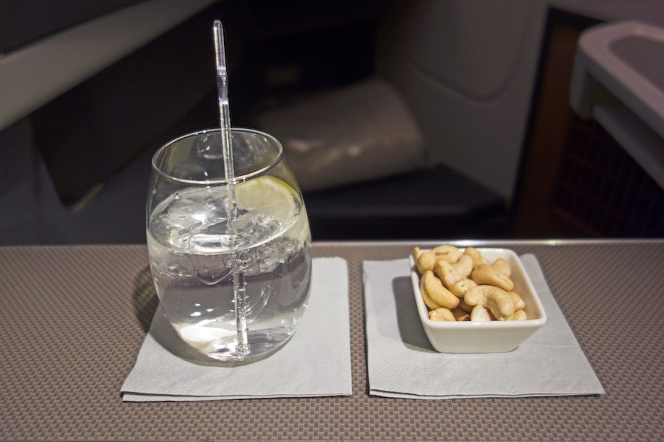 refreshing cocktail with lemon and ice and a dish of delicious hot chew nuts