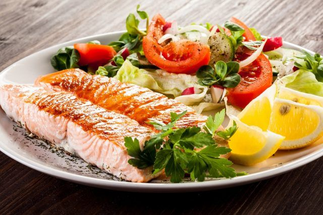 Salmon, vegetables and salad on a plate.