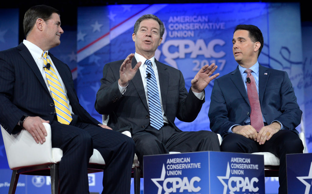 Kansas Gov. Sam Brownback, center, makes remarks during a panel discussion with Arizona Gov. Doug Ducey, left, and Wisconsin Gov. Scott Walker.
