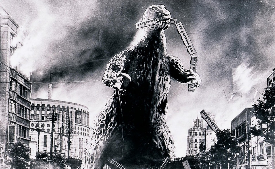 Godzilla in black and white, smashing through downtown, and biting off the end of a train