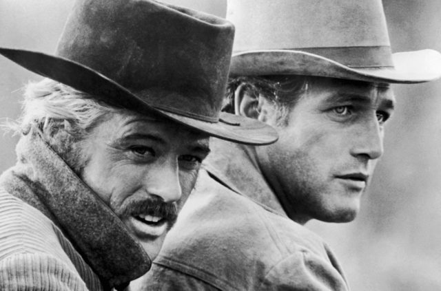 Robert Redford and Paul Newman in black and white, wearing cowboy hats and looking off to the right of the frame