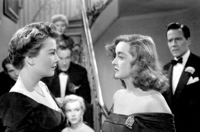 Bette Davis and Anne Baxter, staring intently at each other in front of a crowd of people