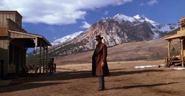 Clint Eastwood in Pale Rider, standing in the middle of a deserted Western town square, with a mountain far in the background
