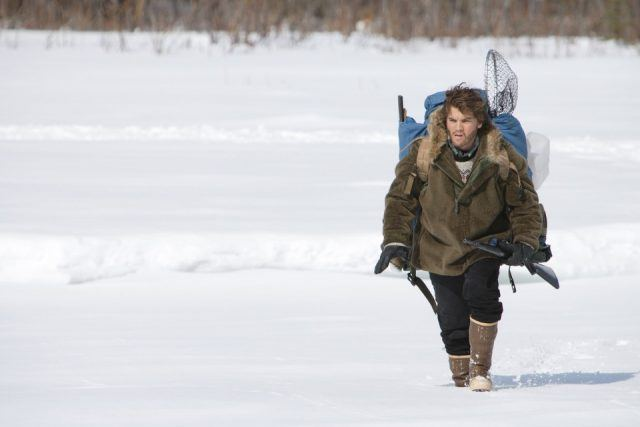 Emile Hirsch, wearing a coat and hiking backpack, trudging through the Alaskan snow