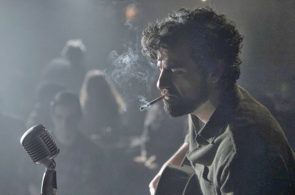 Oscar Isaac, smoking a cigarette on-stage, and playing a guitar
