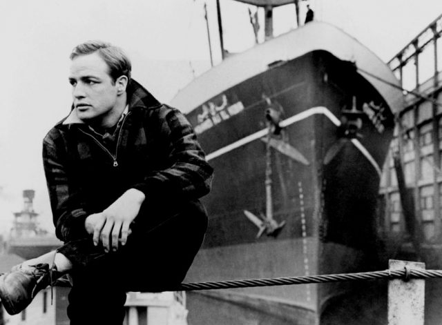 Marlon Brando crouching next to a ship on a dock, looking off over his right shoulder