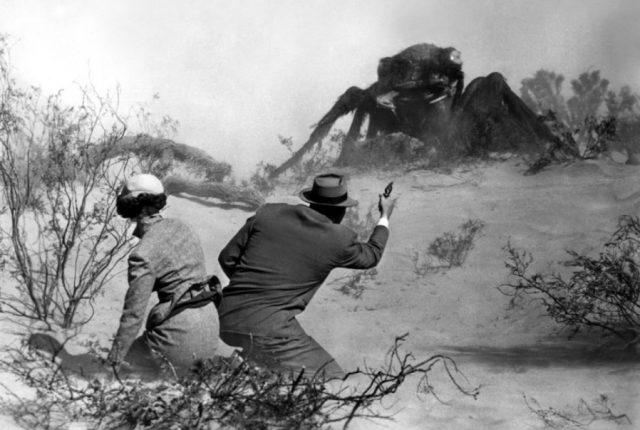 A giant ant off in the distance of a desert, while a man and a woman crouch down in the foreground