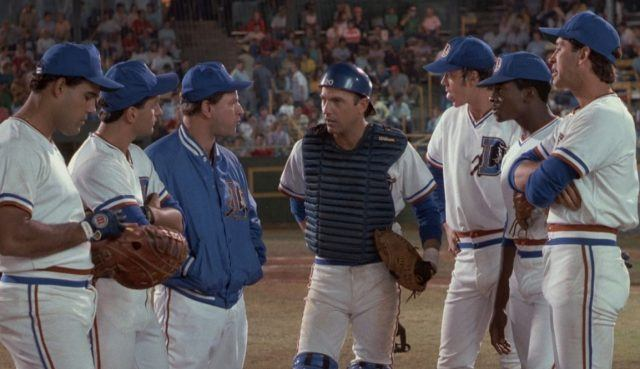 A group of baseball players stand together on the mound, having a conversation