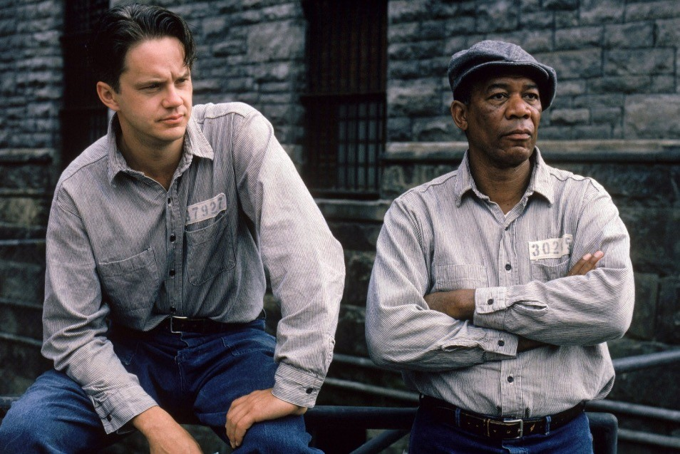 Tim Robbins and Morgan Freeman, sitting and standing respectively, looking off into the distance to the right of the frame
